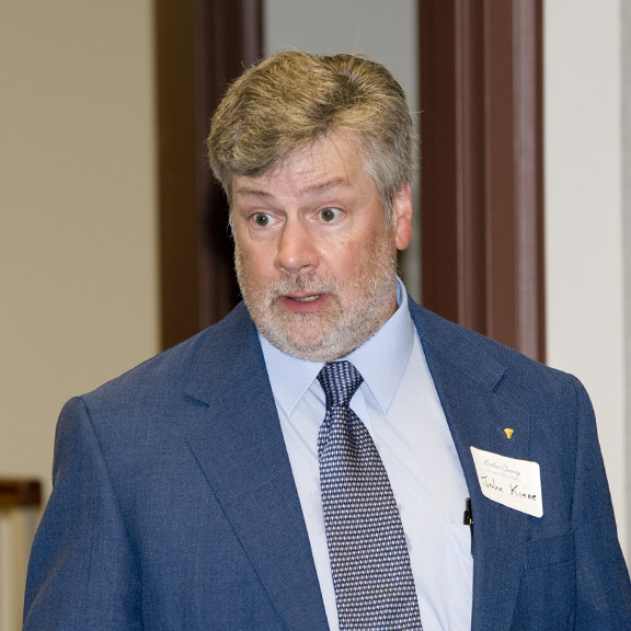 John Kinne in a blue suit, wearing a name tag and talking