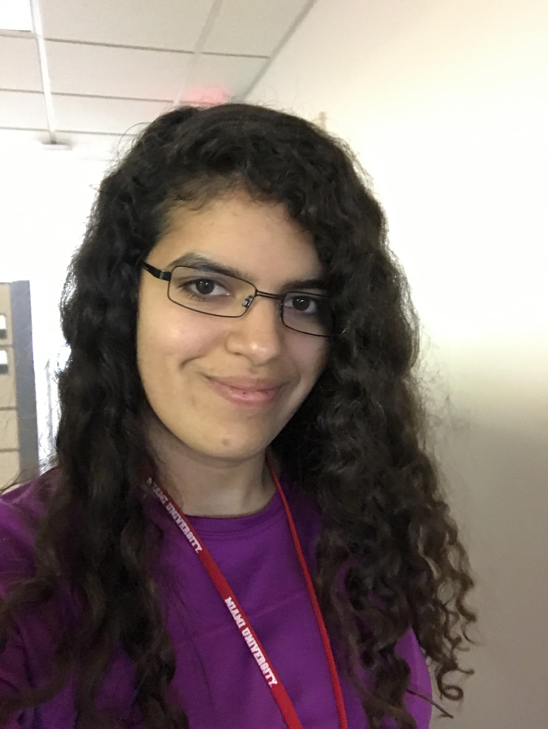 Sofia Olaya wearing a purple shirt, glasses and a red Miami lanyard