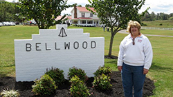 Cindy Hurley standing next to a sign that says Bellwood
