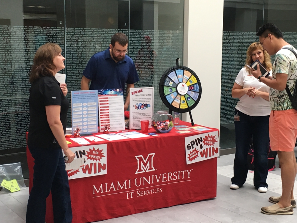 IT Services security awareness table with prize wheel and Connie Johnson, Lisa Raatz and Chris Linebrink assisting a student
