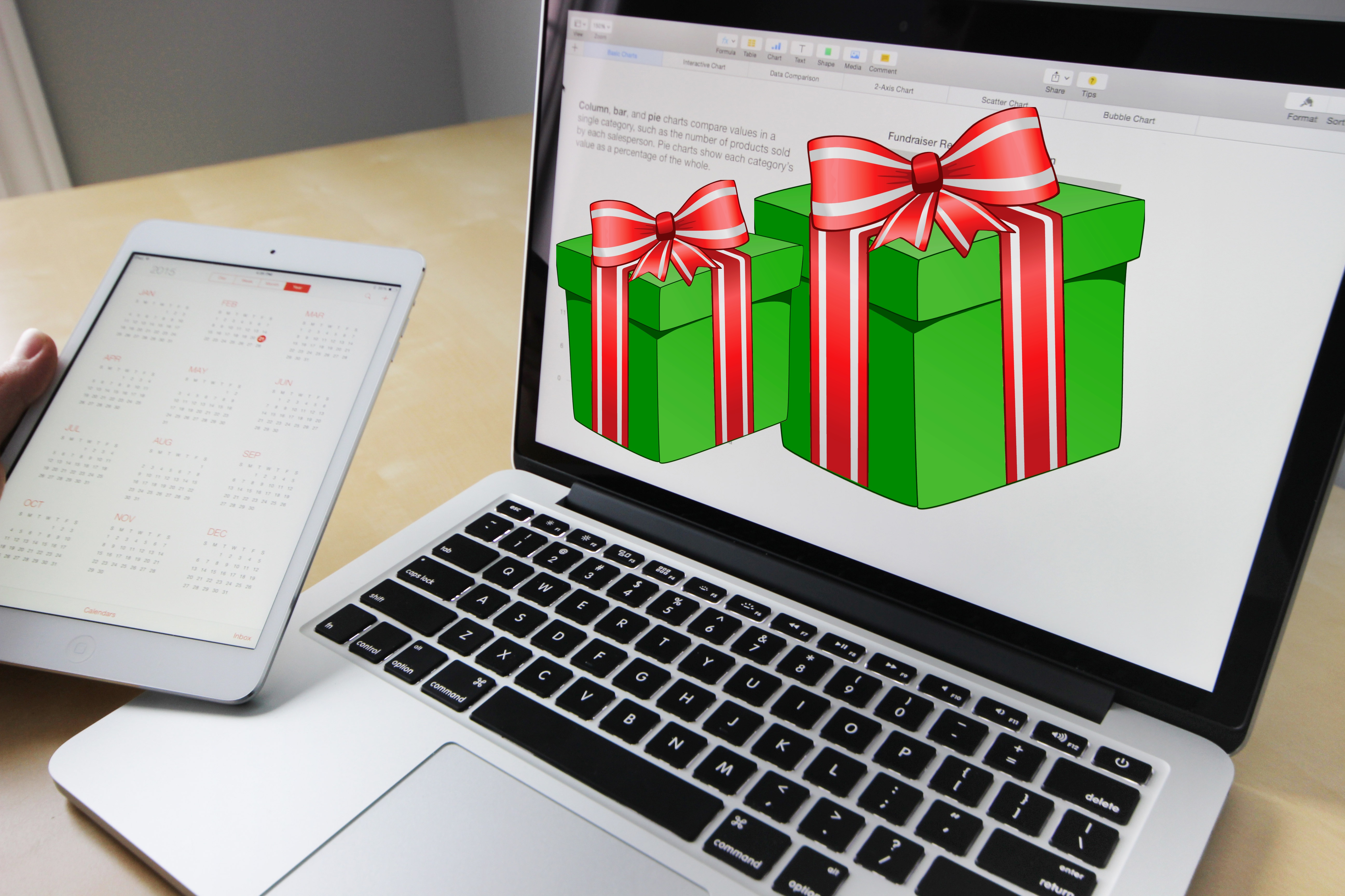 Laptop computer showing two holiday gifts on the screen with green boxes and red and white bows
