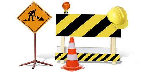 Road construction sign standing next to a yellow and black construction barrier with a yellow hard hat resting on it. In front is an orange and white traffic cone.
