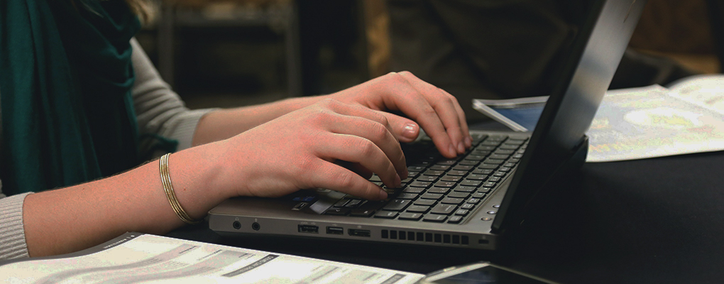 Hands perched above a laptop keyboard