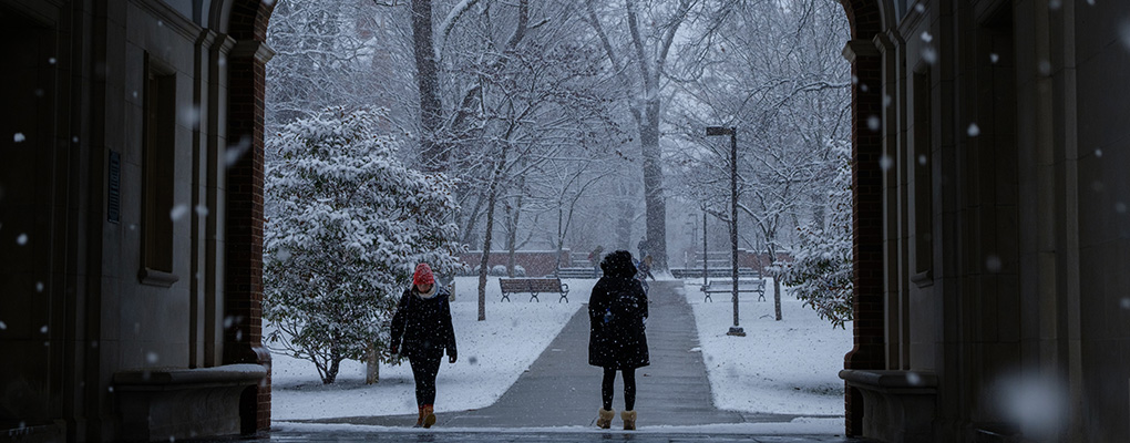 Winter scene, two students wrapped in cold-weather gear walk in the snow on campus.