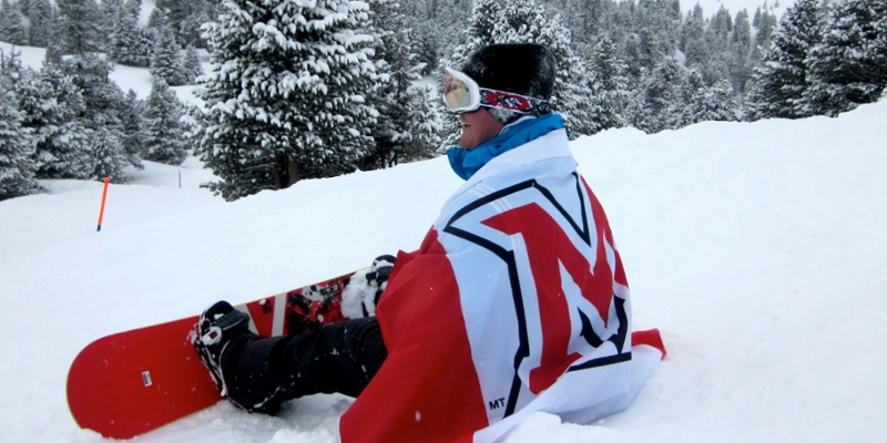 A snowboarder draped in a Miami flag rests facing away from the camera