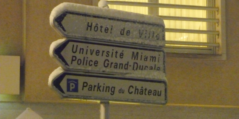 Snow-flocked street signs point to the chateau and other locations in Differdange