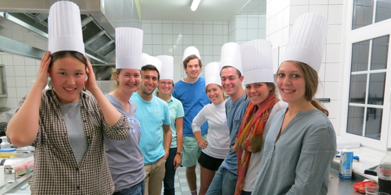Students wearing chefs hats pose in a kitchen