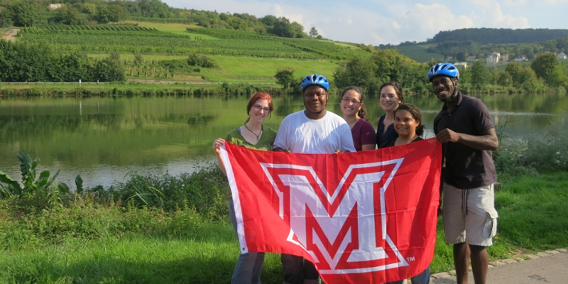 A group of students pose near a river with an unfurled Miami M flag
