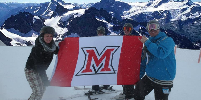 Students pause from skiing to unfurl a Miami M flag on a mountaintop