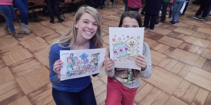 A student and child pose with Easter drawings done during an event with local children