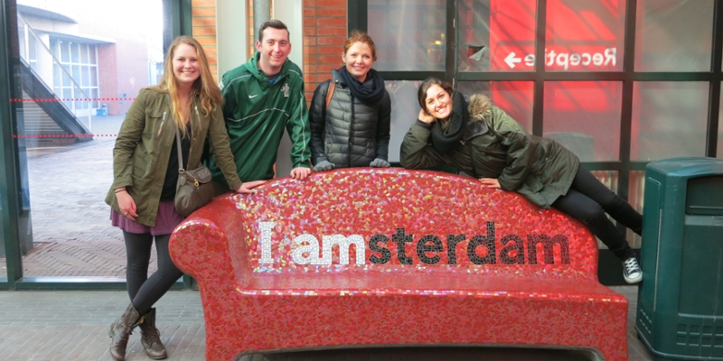 Students pose in Amsterdam near a whimsical bench