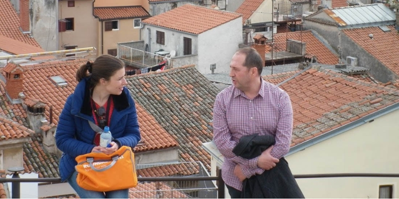 A student and professor chat in front of rooftops below them