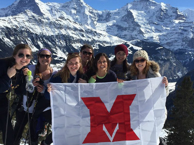 Students hold a Miami M banner while enjoying winter sports in Interlaken