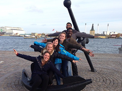 Students with outstretched arms strike a comical pose at the waterfront in Denmark