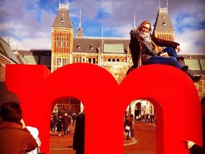 A student strikes a comical pose on top of a sculpture displaying a red lowercase M