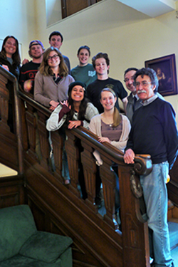 Professor and students pose on a stairway