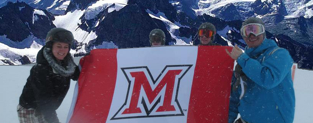 Students skiing in the mountains stop to pose with the M Miami flag