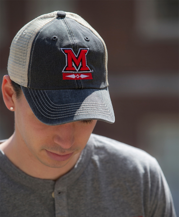 A student looking downward wears a grey and white trucker cap, with large red 'M' and Myaamia logo