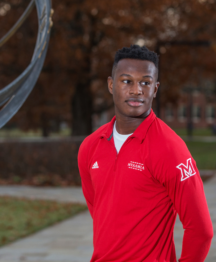 Student stands next to the sundial on central quad. He wears a red quarter zip pullover. The shirt design includes the myaamia heritage logo, Miami University logo, the Adidas logo, and the word 'myaamia'