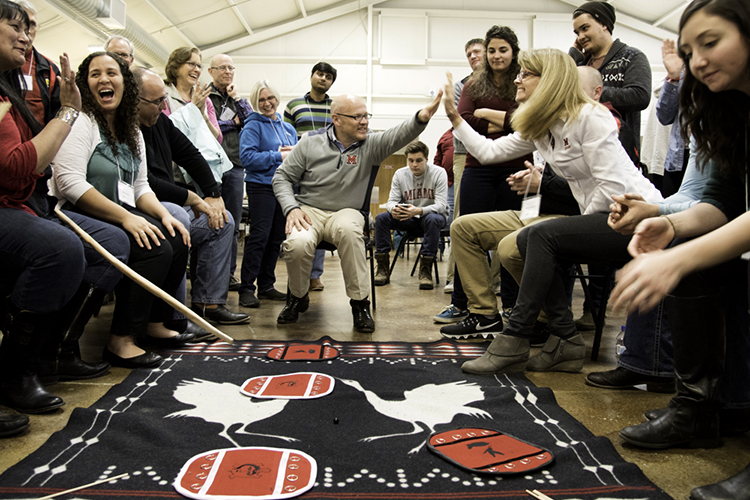 President Crawford and his wife Dr. Crawford participate in moccasin game with MTO members and students