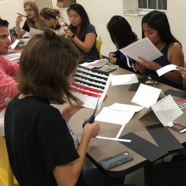 Students creating paper ribbonwork at residence hall event