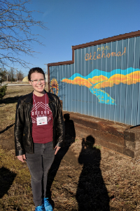 Alyse Capaccio standing in front of a Welcome to Oklahoma sign