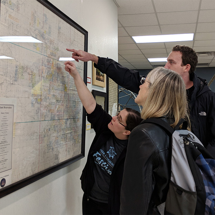 People study a map of tribe land allotments in a museum exhibit