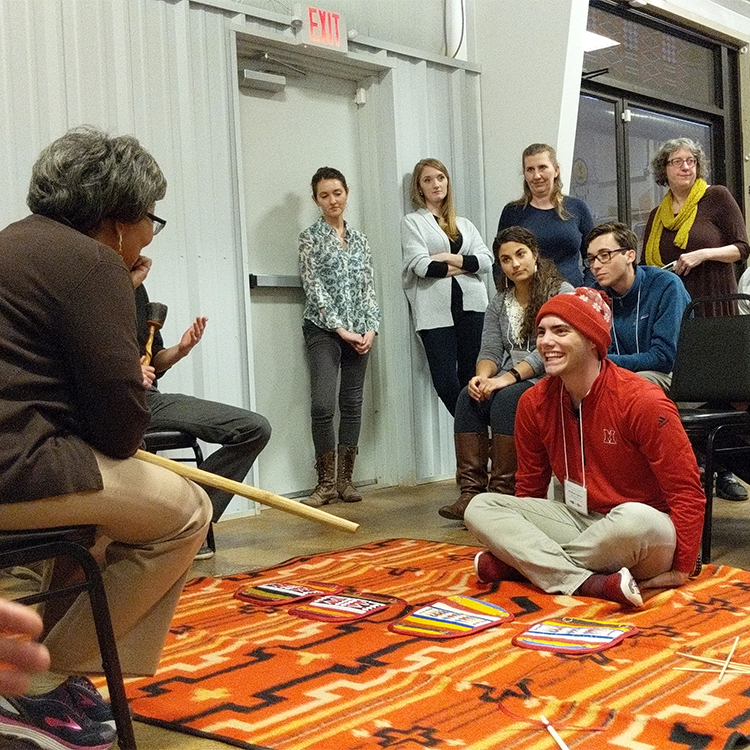 Students and staff play the moccasin game