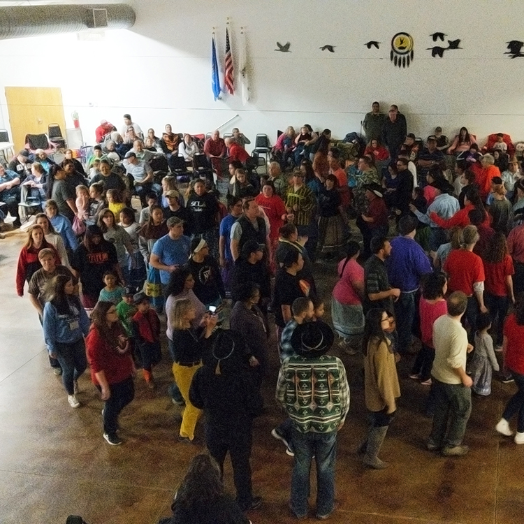 A large group of people, moving in a counter-clockwise circle, participate in the stomp dance