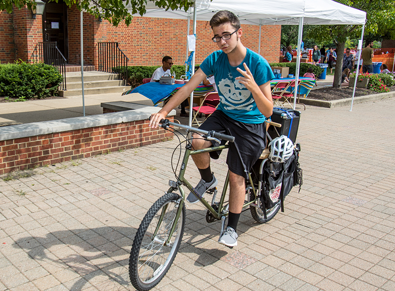 A male student rides a bike while holding up two fingers