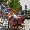 A girl rides in a recliner chair that is attached to a bike driven by a male student