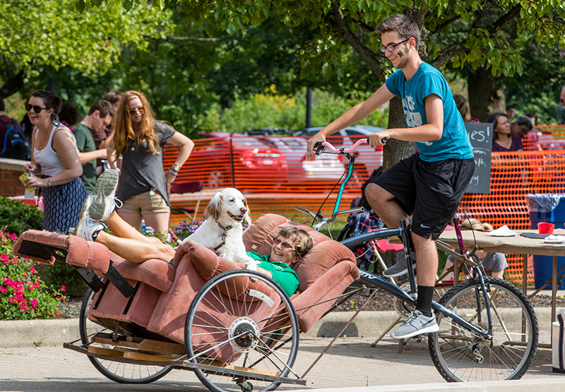 A lady and a dog ride in a recliner chair that is attached to a bike driven by a male student