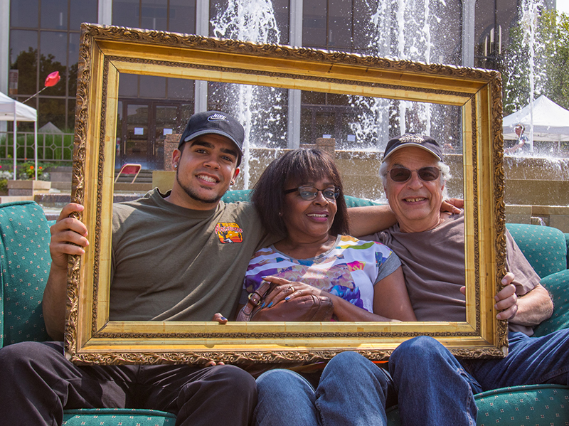 A student sits on a couch with two adults holding up a picture frame in front of them
