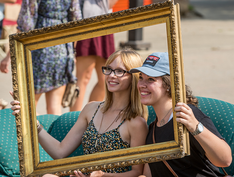 Two female students sitting on a couch posing for a picture while holding up a gold picture frame