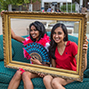 Two girls sit on a couch posing for a picture while holding up a gold picture frame