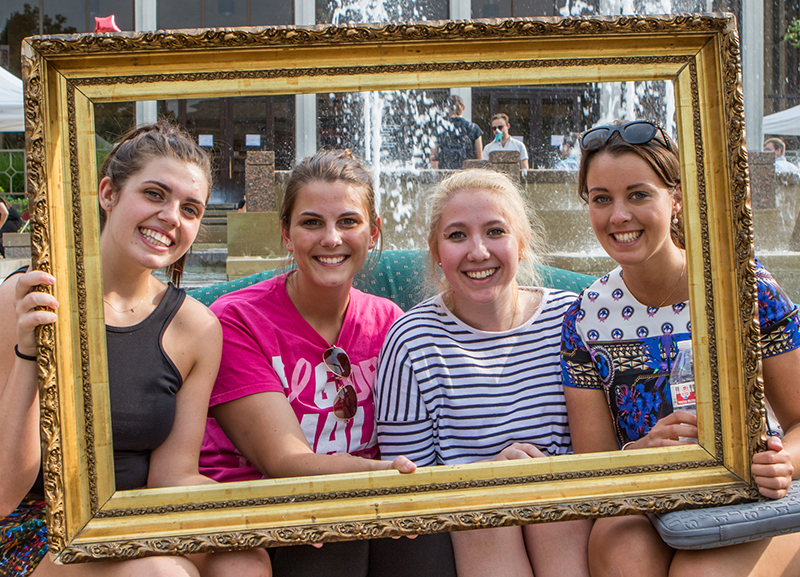 Four girls sit on a couch posing for a picture while holding up a gold picture frame