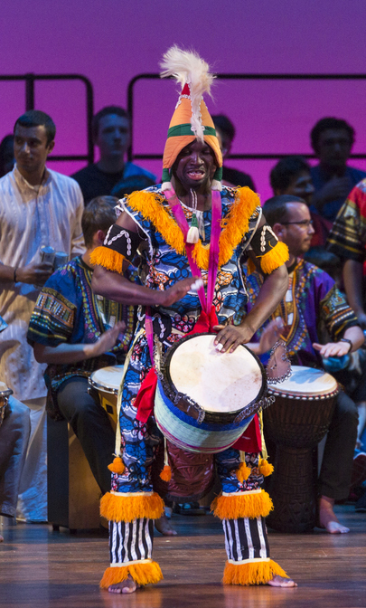 A man dressed in very bright and colorful clothes plays the drums while standing on stage