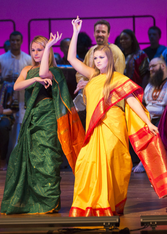 Two females dressed in colorful clothes dance on stage