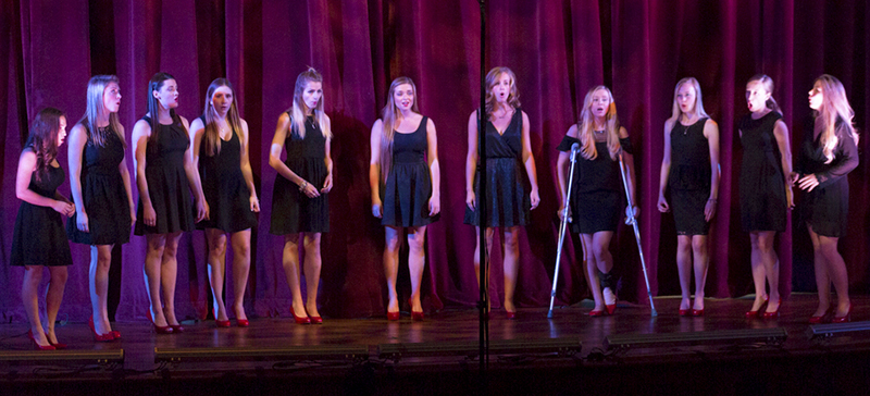 A group of females wearing black dresses and red shoes stands on stage singing