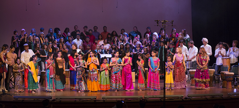The entire group of dancers and musicians stand on stage at the end of the performance