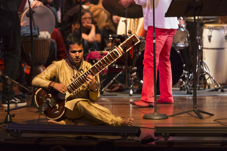 A man sits on the stage while playing a sitar
