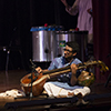 A man sits on stage and plays a sitar