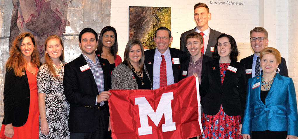 The Miami University Cleveland Alumni Board holding a Miami flag with President Hodge