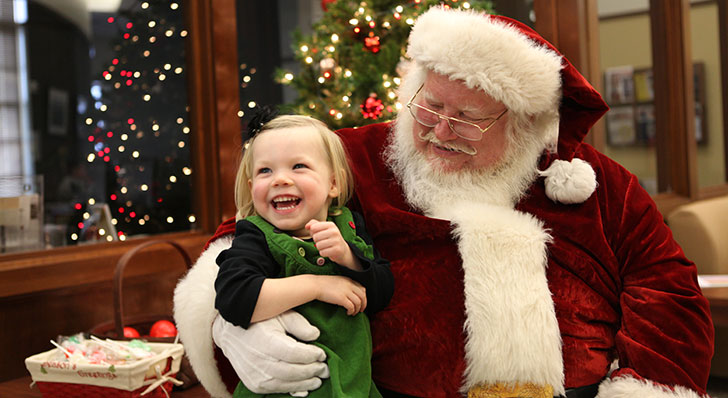 Lila Miller, age 2, visits with Santa Claus at Miami's Voice of America Learning Center