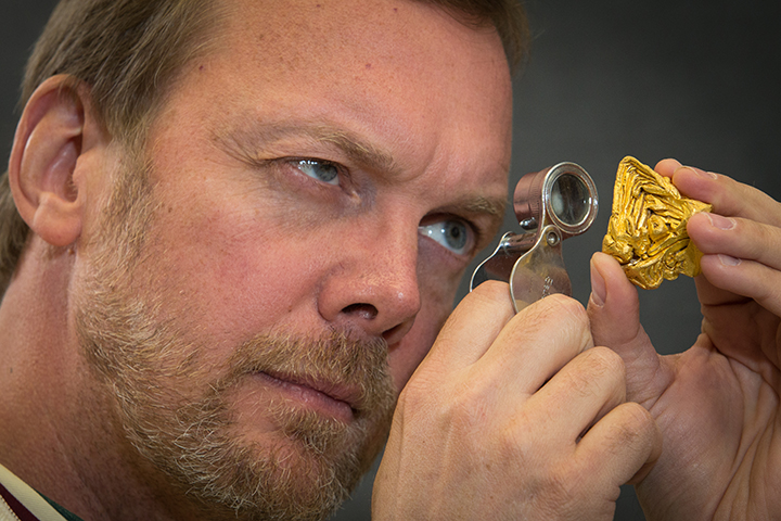 John Rakovan, professor of geology, examines the world's largest single crystal of gold