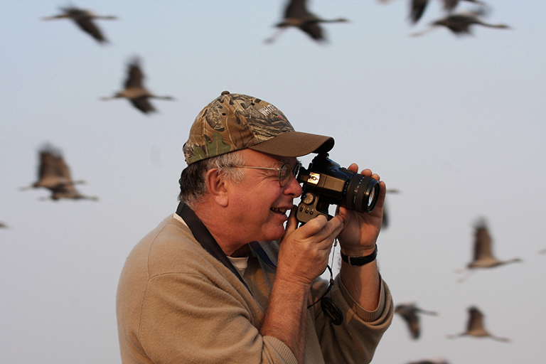 George Archibald leverages the charisma of cranes to unite people from diverse cultures and countries to work together to preserve the landscapes necessary for the survival of both cranes and people. Above, he shoots photos at Keechan, a site in northwestern India where Demoiselle Cranes winter (photo courtesy International Crane Foundation).