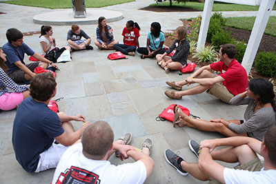 Students outside sitting in a circle discussing the summer reading selection