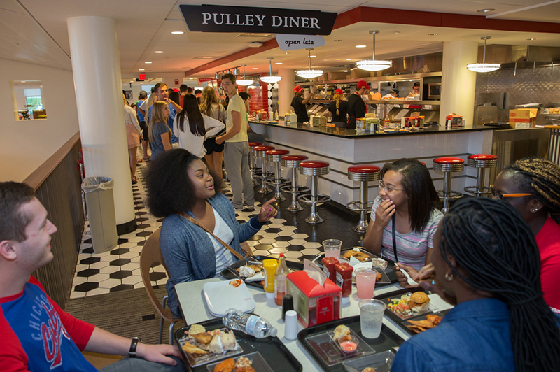 A group of students talk over snacks at the pulley diner
