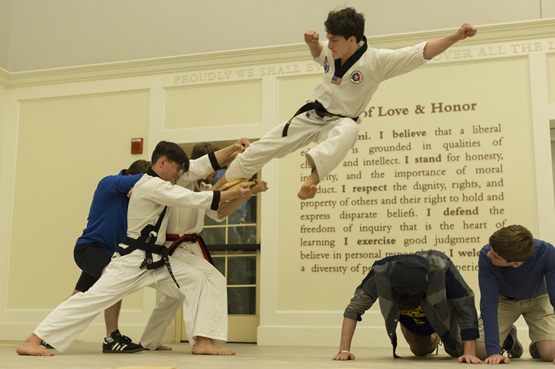A blackbelt jumps over two students on their hands and knees and breaks a board in a Taekwondo demonstration in the Shade Family Room