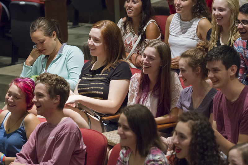 Students sitting in the Wilks Auditorium smile as they watch a performance